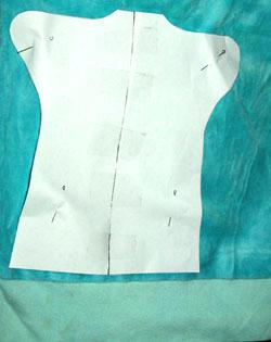 Выкройка частей костюма на ткани.